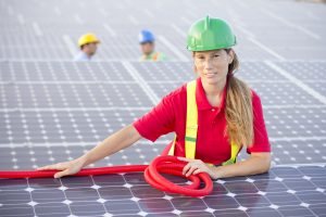 Image of a female worker in the foreground at a  photovoltaic farm looking at camera. All my images have been processed in 16 Bits and transfer down to 8 before uploading.