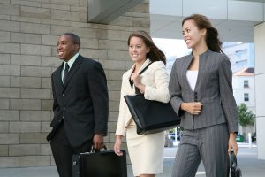 An attractive business team walking composed of two women and a man